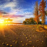 Arc in autumnal city park at sunset. Fallen leaves Stock Image