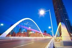 Arc bridge girder highway car light trails city night landscape. Modern city highway arc bridge night landscape of car light trails Royalty Free Stock Photography