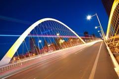 Arc bridge girder highway car light trails city night landscape. Modern city highway arc bridge night landscape of car light trails Stock Photography