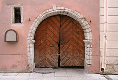 Arc with Brown wooden gate. Fragment of an ancient build with brown wooden gate Royalty Free Stock Photo