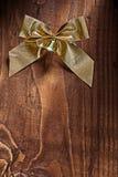 Arc d'or simple de Noël avec la petite cloche sur le vieux conseil en bois Photos libres de droits