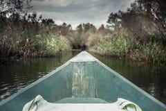 Arc de bateau avec la direction en avant vers la banque sur la rivière dans le jour obscurci avec le ciel dramatique symbolisant  Photos libres de droits