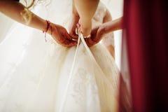 Arc de lien de demoiselles d'honneur sur la robe de mariage de la jeune mariée Photos libres de droits