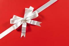 Arc de ruban de cadeau de cadre de frontière de Noël, fond de papier rouge, diagonale faisante le coin Photographie stock