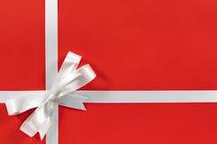 Arc de ruban de cadeau de cadre de frontière de Noël sur le fond de papier rouge Images stock