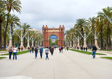 The Arc de Triomf. Barcelona, Spain - April 4, 2016: Day view to The Arc de Triomf. Crowd of people walking along the pedestrian street of the Passeig de Lluis Royalty Free Stock Image