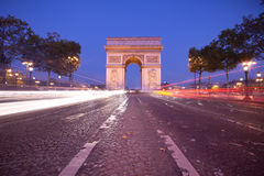 Arc de Triomphe. Front view of Arc de Triomphe (Arch of Triumph) in Paris at dusk with traffic light trail Stock Photography