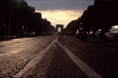 Arc de Triomphe. View of the Arch at sunset. Blurred cars in the right side Stock Photos