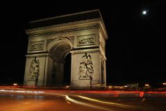 Arc de Triomphe / Arc de Triumph at night, shining trails of traffic and moon, Paris, France. Arc de Triomphe / Arc de Triumph at night, clear black sky, shining Stock Photos