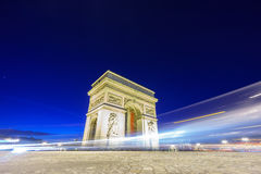 Arc de Triomphe and blurred traffic at night. Night time in Arc de Triomphe and blurred cars traffic along the traffic circle Royalty Free Stock Images