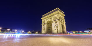 Arc de Triomphe and blurred traffic at night. Night time in Arc de Triomphe and blurred cars traffic along the traffic circle Royalty Free Stock Photography