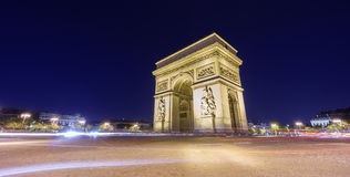 Arc de Triomphe and blurred traffic at night. Night time in Arc de Triomphe and blurred cars traffic along the traffic circle Stock Photo