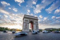 Arc de Triomphe and blurred traffic at sunset. Sunset with dramatic sky behind Arc de Triomphe and blurred cars traffic along the Champs-Elysees Royalty Free Stock Images