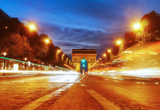 Arc De Triomphe from a busy Champs Elysees at Night. A time lapse of the Champs Elysees with traffic heading to the Arc De Triomphe Royalty Free Stock Photo