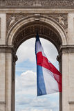 Arc de Triomphe detail and French flag. On a sunny day Stock Photos