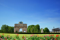 Arc de Triomphe du Carrousel Paris France. Arc de Triomphe du Carrousel on a blue sky background. A lawn and tulips are in the foreground. Place du Carrousel Royalty Free Stock Photos