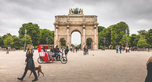 The Arc de Triomphe du Carrousel in Paris. Paris, France - May 08, 2017 : In the garden of the tuileries, tourists walk before the triumphal arch of the carousel Stock Images