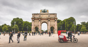 The Arc de Triomphe du Carrousel in Paris. Paris, France - May 08, 2017 : In the garden of the tuileries, tourists walk before the triumphal arch of the carousel Stock Image