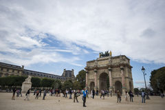 Arc de Triomphe du Carrousel. The Arc de Triomphe du Carrousel standing tall with a crowd of people walking below on a sunny day, Paris, France Royalty Free Stock Images