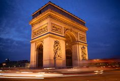 Arc de Triomphe at Dusk. Rush hour traffic drives around the Arc de Triomphe in Paris, France Stock Photo