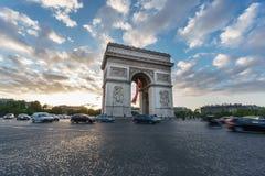 Arc de Triomphe et le trafic brouillé au coucher du soleil Photos stock