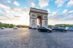 Arc de Triomphe et le trafic brouillé au coucher du soleil, grand-angulaire Photo stock