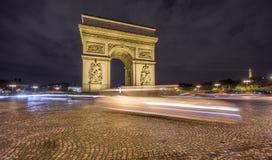 Arc de Triomphe et le trafic brouillé la nuit Images stock