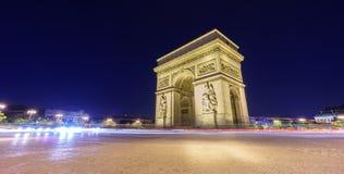 Arc de Triomphe et le trafic brouillé la nuit Photographie stock libre de droits