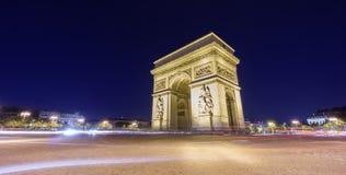 Arc de Triomphe et le trafic brouillé la nuit Photo stock