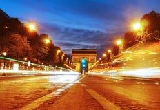 Arc de Triomphe från ett upptagna Champs-Elysees på natten Royaltyfri Foto