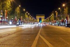 Arc de Triomphe i Paris, Frankrike under rusningstid på natten Traf royaltyfria foton