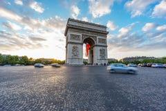 Arc de Triomphe large et le trafic brouillé au coucher du soleil Images libres de droits