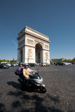 Arc De Triomphe Motorcyclist Traffic. Paris, France - July 5, 2011:  A motorcyclist and passenger take a turn away from the Arc de Triomphe onto Champs d'Elysees Stock Images