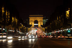 Arc de Triomphe at night. Arc de Triomphe and Champs-Elysees Avenue in Paris at dusk Royalty Free Stock Images