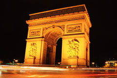 Arc De Triomphe at Night. Night shot of the  Arc De Triomphe in Paris France with a slow exposure showing light trails left by passing cars Royalty Free Stock Photos