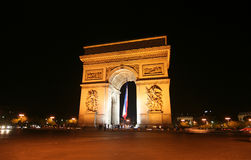Arc de Triomphe at Night. Arc de Triomphe with French flag at night royalty free stock photo
