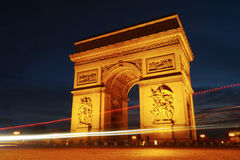 Arc De Triomphe at night in traffic. The Arc De Triomphe surrounded by traffic and visitors at the iconic landmark Royalty Free Stock Photography