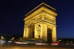 Arc de Triomphe på natten i färg med billjus skuggar Fotografering för Bildbyråer