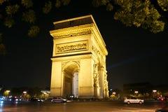 Arc de Triomphe Parijs, Frankrijk in geel licht bij nacht wordt aangestoken die stock fotografie