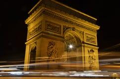 Arc de Triomphe in Parijs, Frankrijk - nachtmening met sporen van auto'slichten stock afbeelding