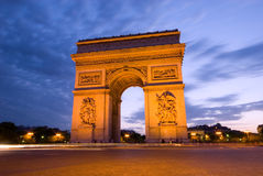 Arc de Triomphe, Paris. The Arc de Triomphe, seen here during twilight and rush hour traffic, is one of Paris' most famous landmark Royalty Free Stock Image
