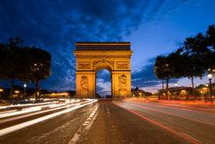 Arc de Triomphe, Paris. The Arc de Triomphe, seen here during twilight and rush hour traffic, is one of Paris' most famous landmark Royalty Free Stock Photography