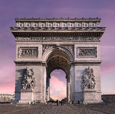 Arc de Triomphe of Paris against a pink sky. The Arch of Triomphe often simply called the Arc de Triomphe, the construction, decided by the Emperor Napoleon I Stock Photos