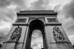 Arc de triomphe Paris city in B&W. The arc de triomphe in paris at a cloudy day with the beautiful sculpture in black and white with a wide angle Royalty Free Stock Images