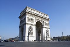 Arc de Triomphe, Paris, with Eiffel Tower. The Arc de Triomphe monument in Paris, France, against a cloudless blue day sky with the Eiffel Tower in the Stock Photo