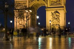 Arc de Triomphe, Paris, France. Tightly-framed photograph of the Arc De Triomphe taken at night with blurred figures in the foreground Royalty Free Stock Photography