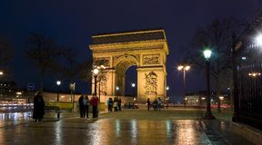 Arc de Triomphe, Paris, France. The Arc de Triomphe at night with street lights and groups of tourists Royalty Free Stock Photography