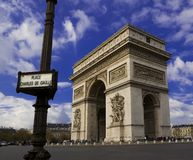 Arc de Triomphe, Paris, France. The Arc de Triomphe in sunshine and blue sky with Place Charles de Gaulle street sign in foreground Royalty Free Stock Image