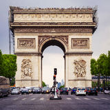 Arc de Triomphe in Paris - France - April 24. 2014. Paris, France - April 24. 2014 : The cars are waiting for green traffic light in front of the Arc de Triomphe Royalty Free Stock Image