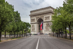Arc de Triomphe in Paris, France. Arc de Triomphe with flag in Paris, France Stock Photography